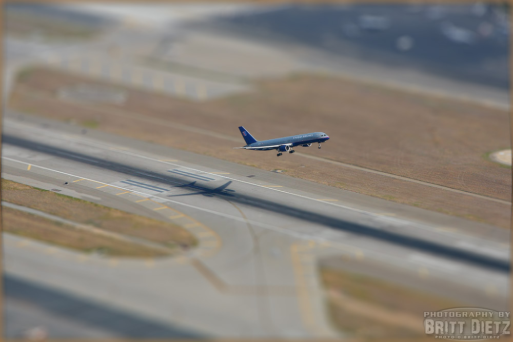 A tilt shift shot of a Boeing 757 taking off from John Wayne Airport