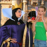 The Evil Queen offers an apple to a guest