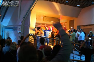 A Cast Member raises his hands in a cheer as the doors are closed