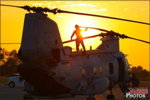 The setting sun shines behind a crew member preparing a CH-46E Sea Knight