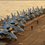 A row of F/A-18C Hornets from various squadrons sit on the forward deck of the USS Abraham Lincoln Aircraft Carrier