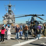 Civilians tour the flight deck of the USS Peleliu US Marine Amphibious Assault Carrier