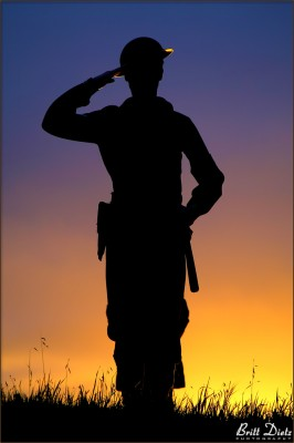 A WW2 Navy Shore Patrol reenactor salutes during dusk at the LA Air Raid 2011 event.